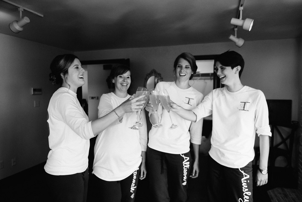 bride and bridesmaids toast with champagne