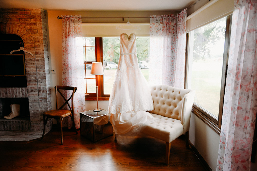 wedding dress hanging in window at landing 1841 wedding