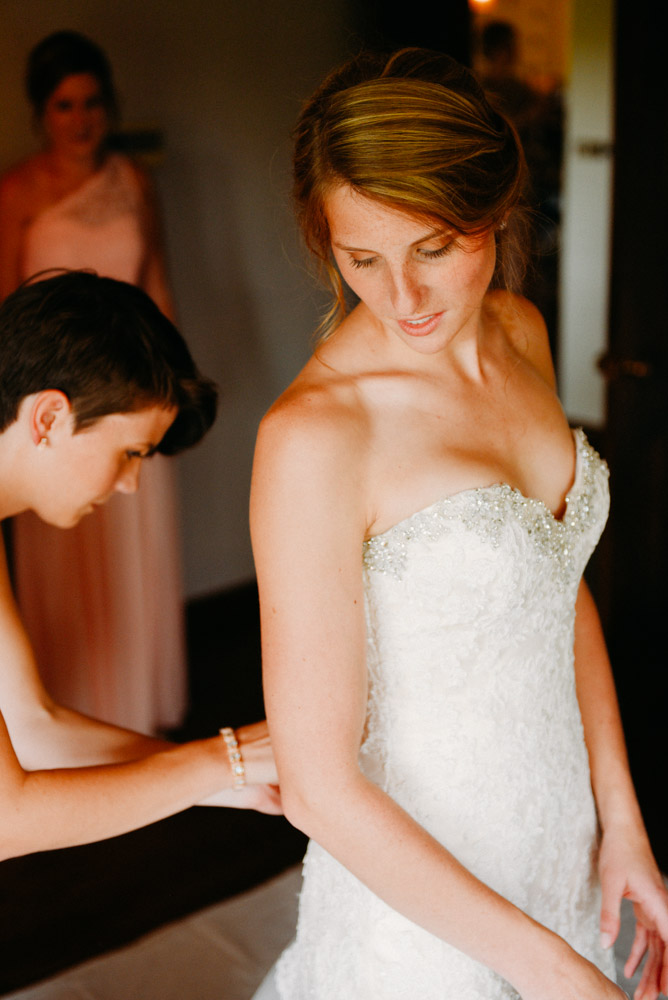 wisconsin bride putting on wedding dress