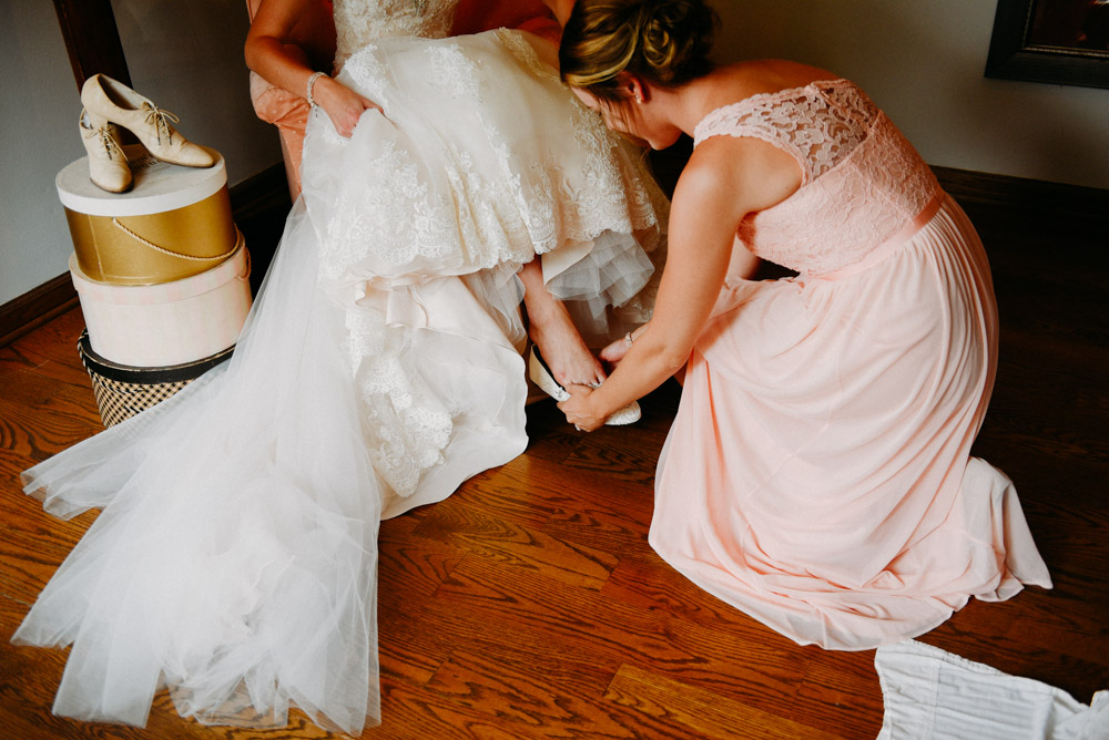bride putting on shoes at landing 1841 wedding in wisconsin