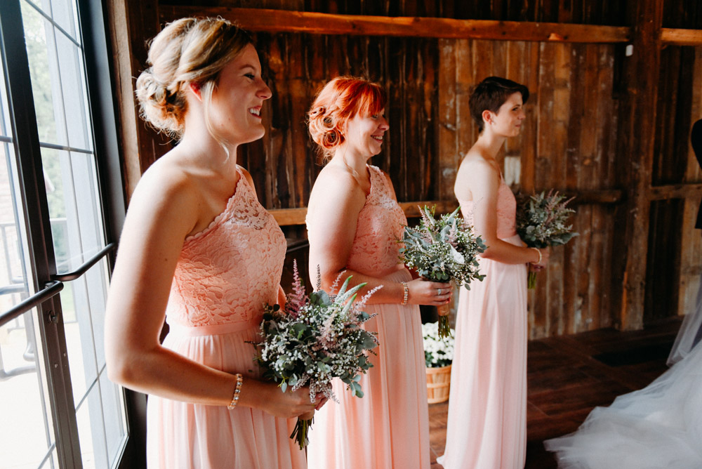 bridesmaids in pink dresses during ceremony