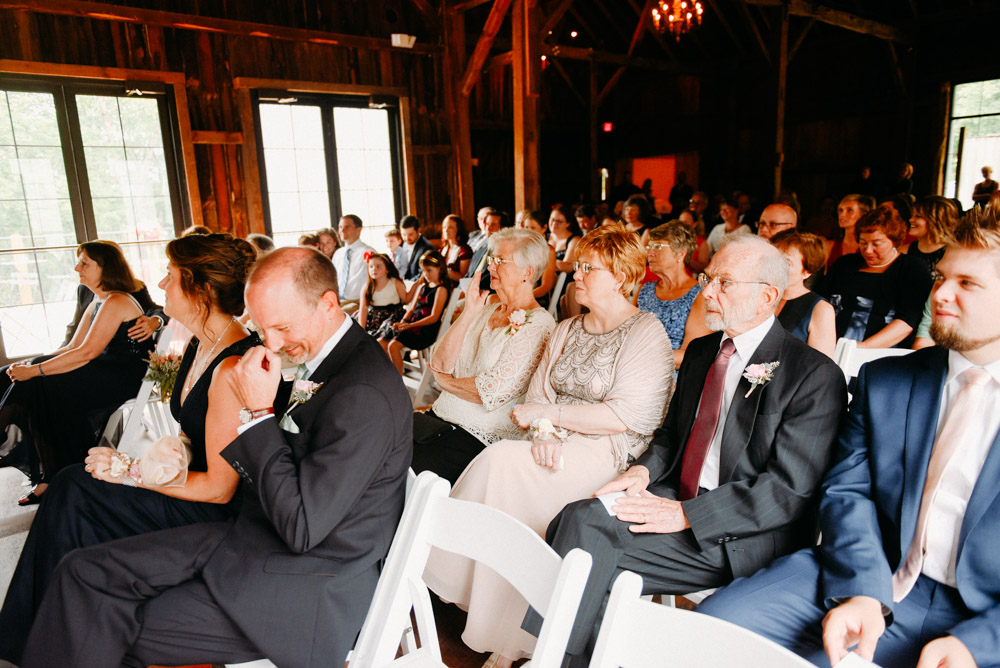 guests seated in naturally lit barn wedding