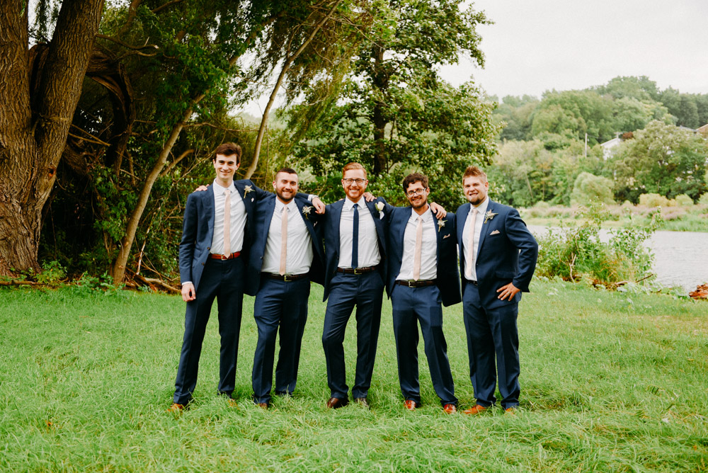 happy groomsmen in blue suits
