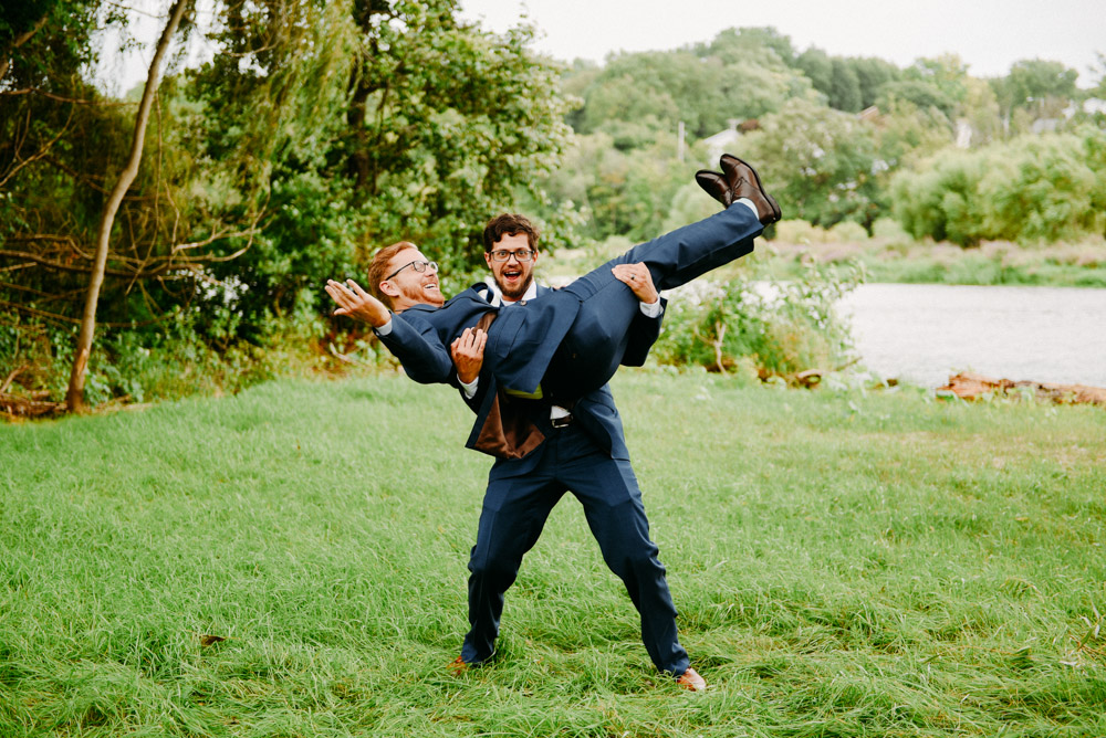 groomsman holding groom in wooded area