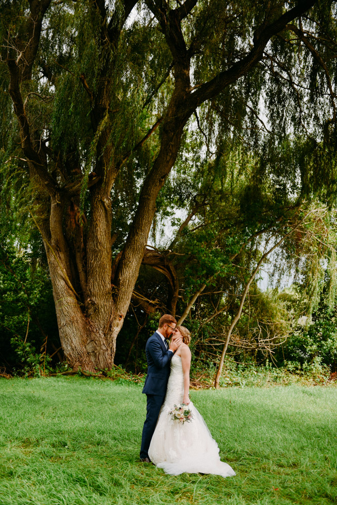 groom caressing bride under willow tree