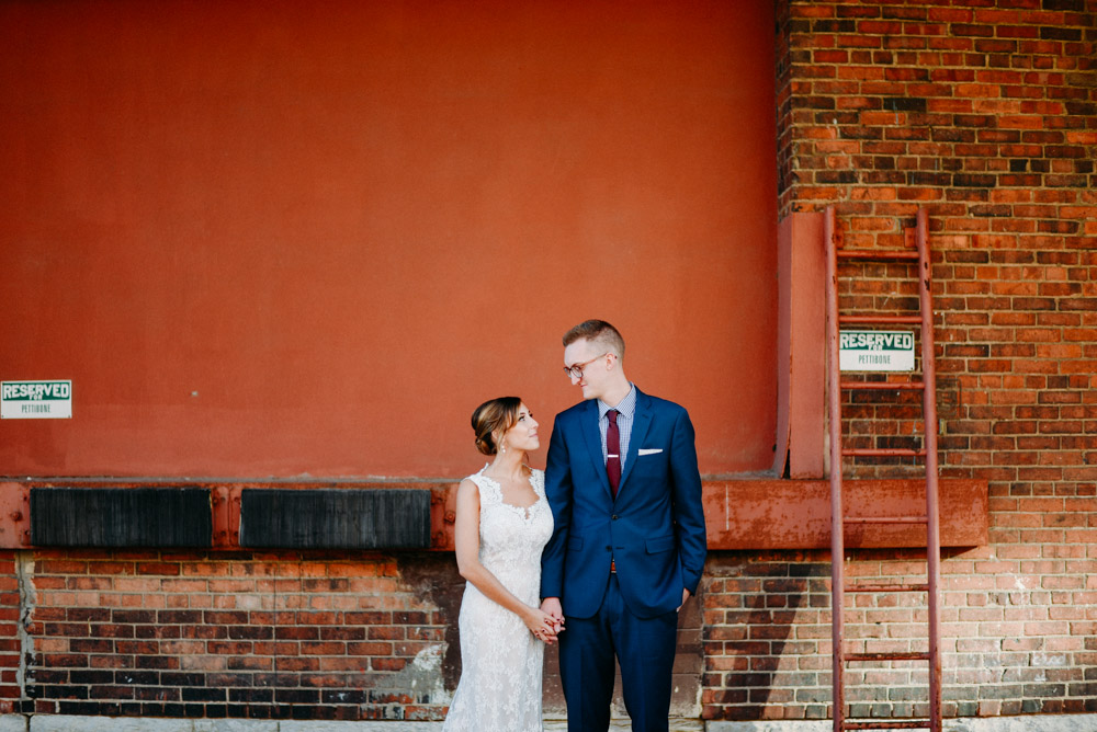 married couple against rustic orange wall