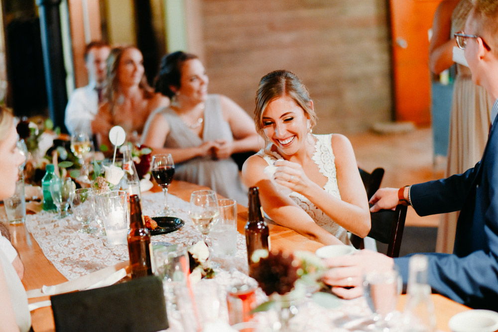 bride laughing at head table