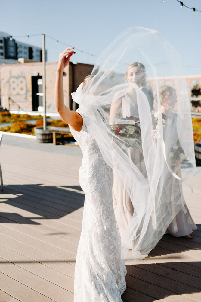 bride playing with long veil in wind