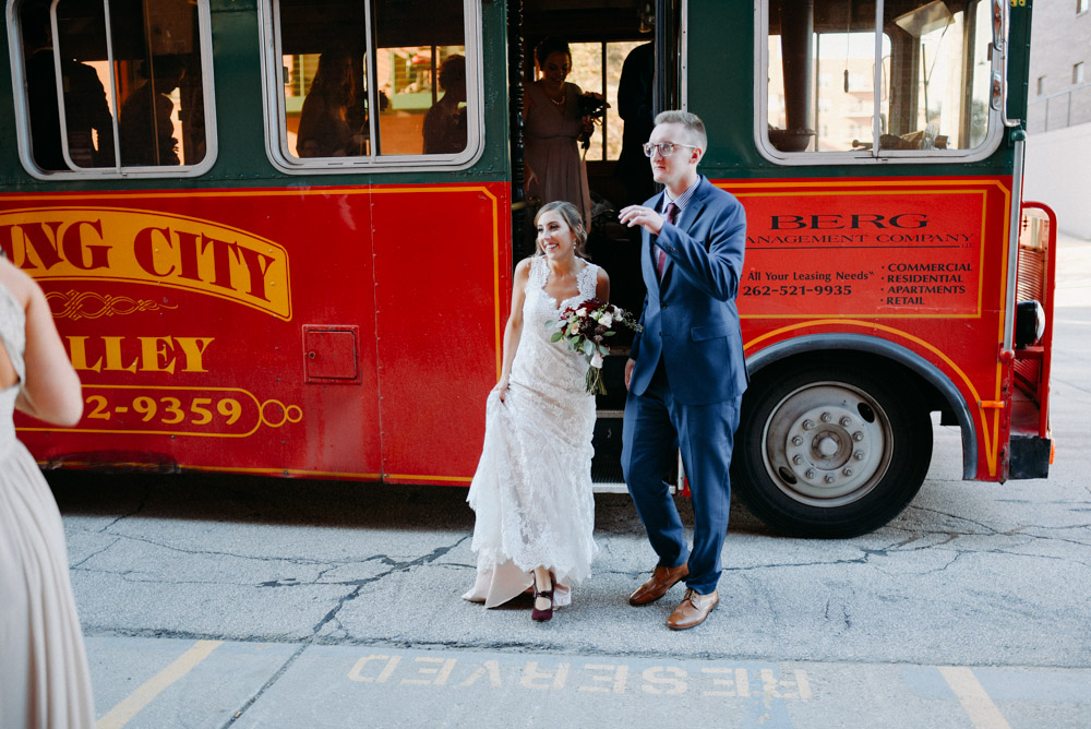 bride and groom getting off of red milwaukee trolley