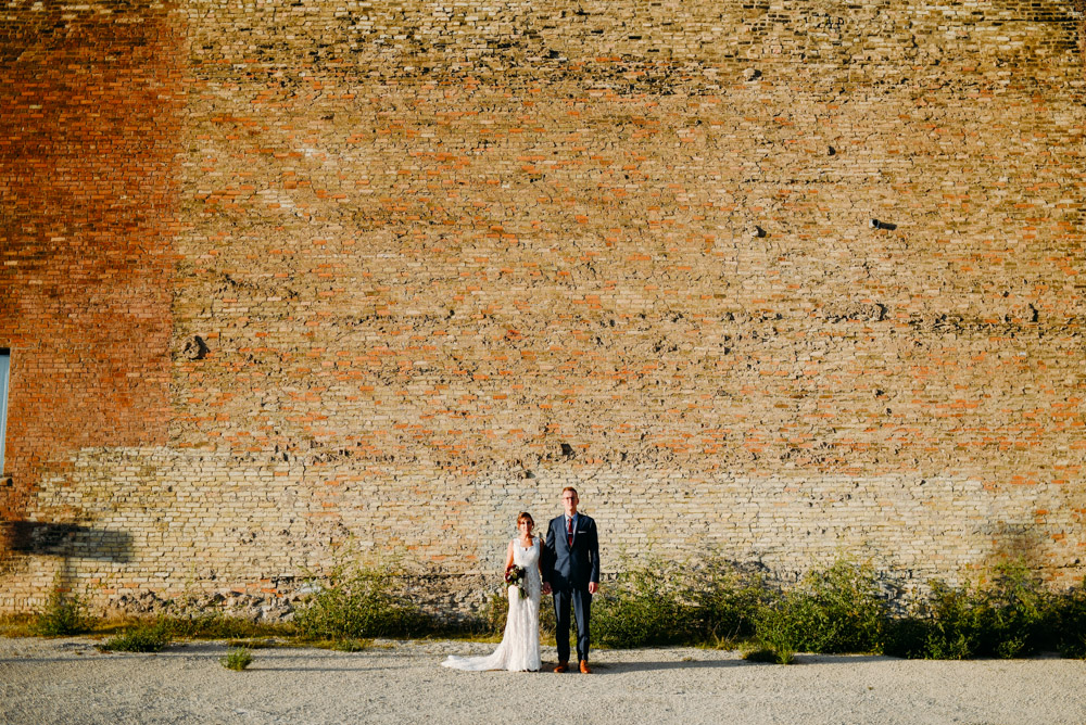 scenic bride and groom against cream city brick wall
