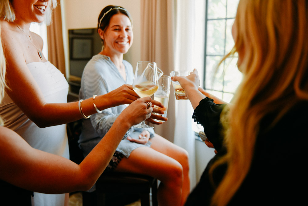 girls clinking glasses while preparing for wedding