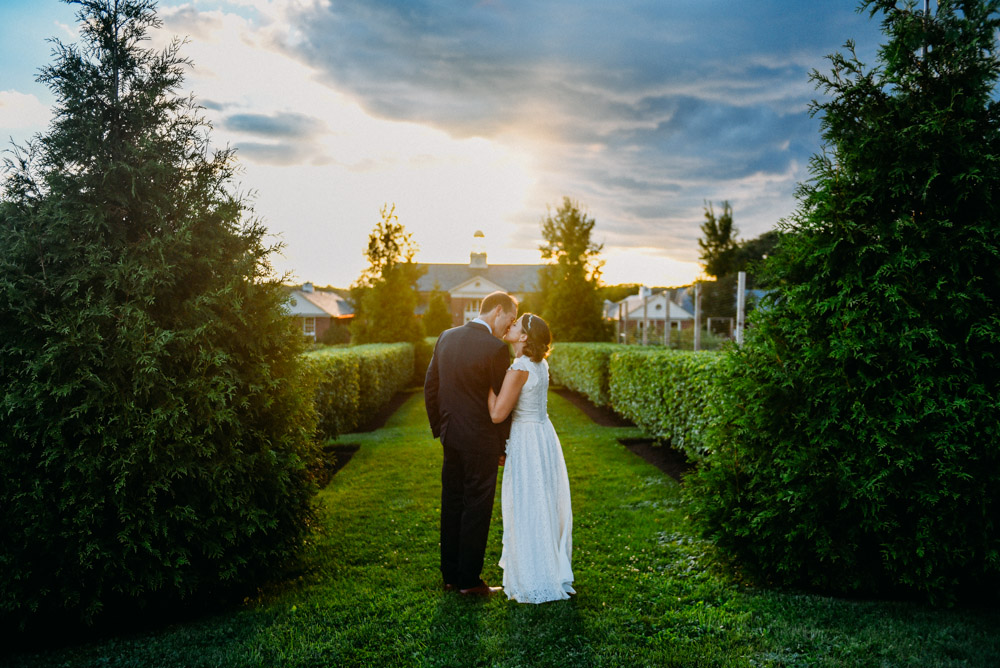 cute couple kissing among hedges after elawa farm wedding
