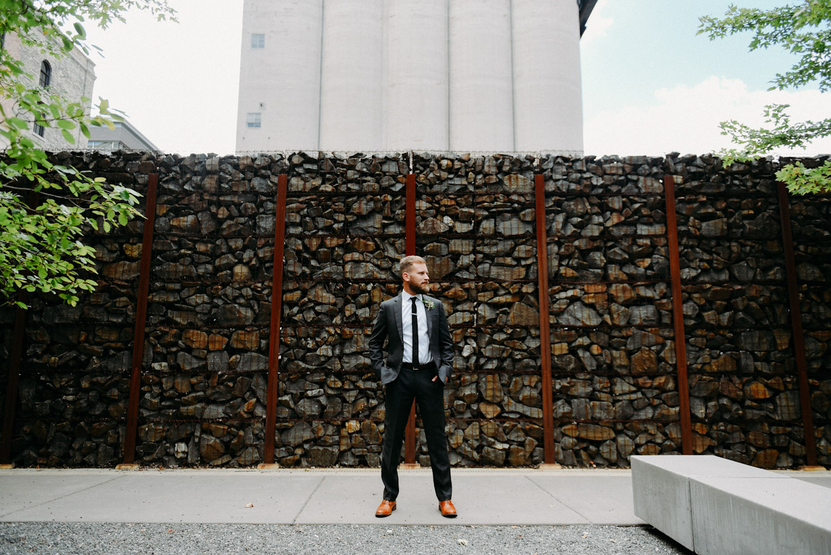 groom portrait against rock wall in milwaukee