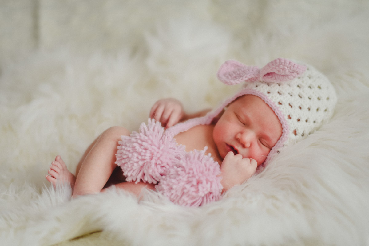 newborn baby in pink hat with pompoms