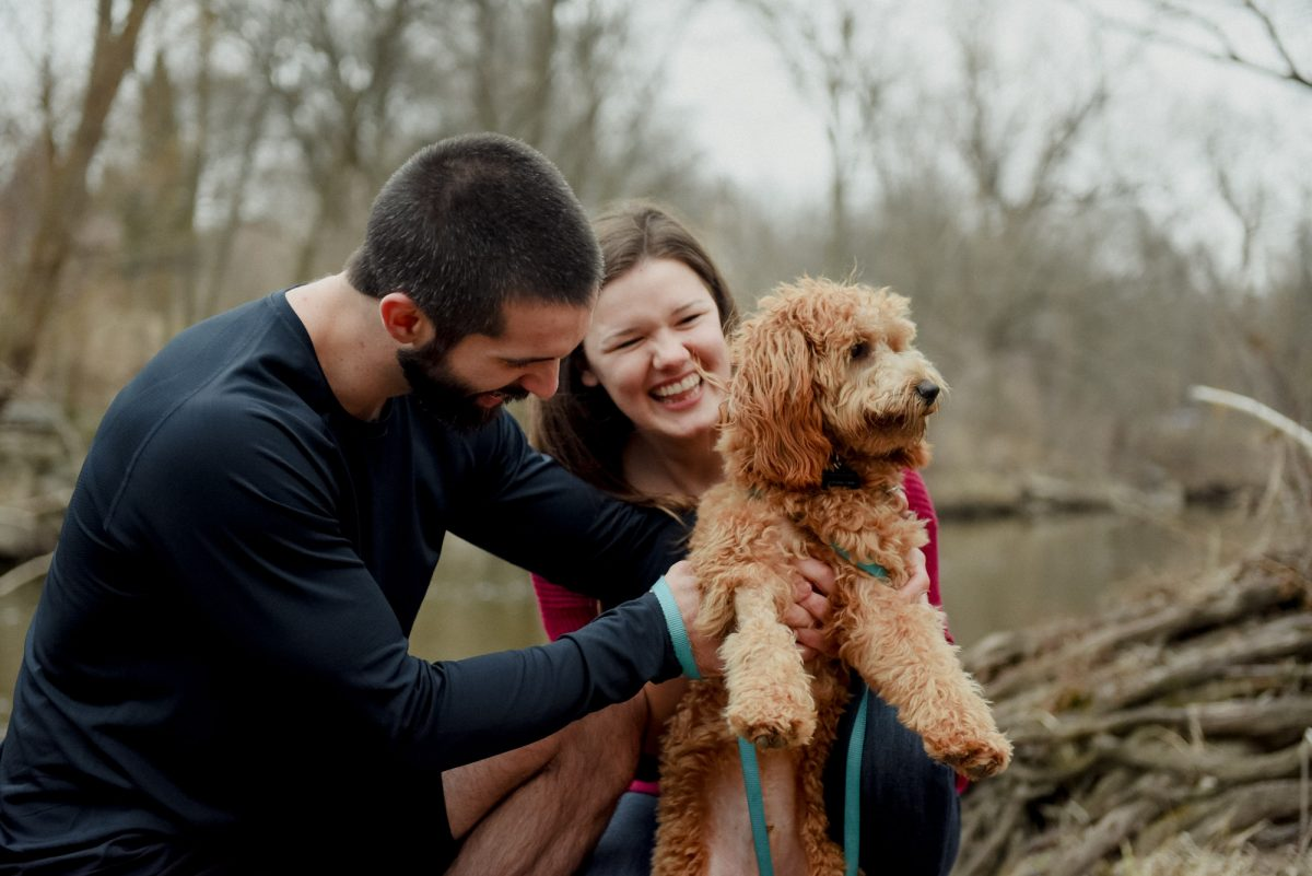 man and woman playing with curly haired puppy
